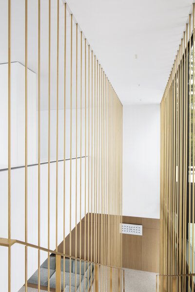 """The brass staircase was one of the costliest elements of the build. """"It was worth investing in [because]  it contributes to defining the ambiance of the house in its two most important rooms—the living and dining [areas],"""" Chevalier states."""
