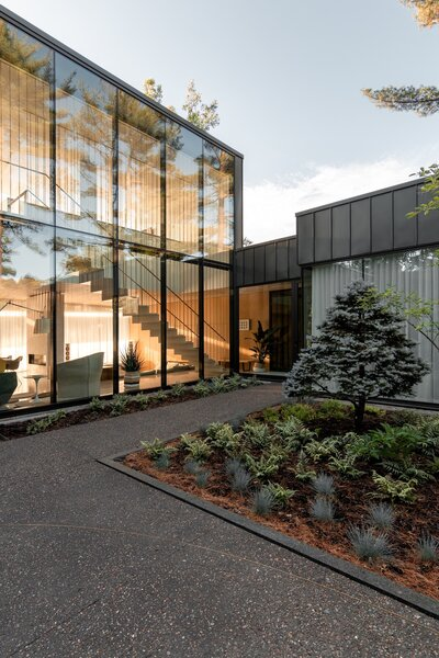 The entrance to the Residence de l'Isle is planted with large coniferous trees.