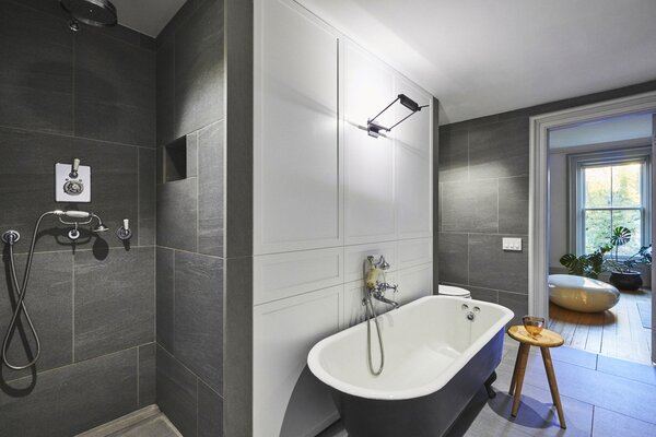 The primary bedroom has an adjoining dressing room and bathroom. The design team salvaged the home's original claw-foot tub and reglazed it to restore it.
