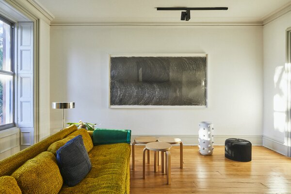 A multiuse room on the second floor functions as a meeting room for the office, a secondary living room, and a guest bedroom. The original pine flooring was restored as part of the renovation.