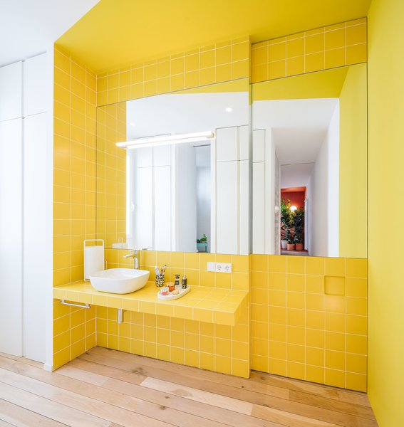 Spanish firm Gon Architects and designer Ana Torres renovated this 69-foot-long Madrid flat to include a yellow-tiled bathroom, salmon-hued bedroom reading nook, and bright-blue kitchen stand. The home's colorful corners are tied together by white passages and subtle wood floors.