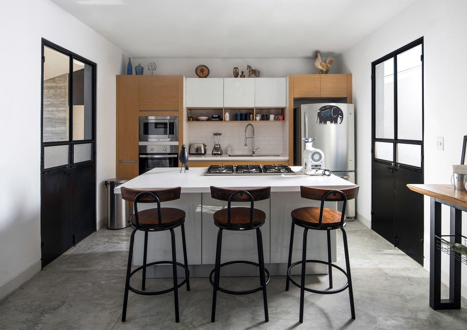 Kitchen, Mosaic Tile Backsplashe, Refrigerator, Concrete Floor, Wall Oven, Beverage Center, Wood Cabinet, Drop In Sink, Ceiling Lighting, Microwave, and Brick Backsplashe Kitchen  Pia Residence