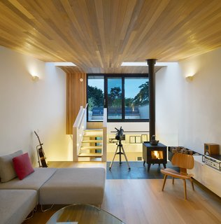 The third floor living room - an urbanized version of a cabin in the woods, with wood stove and cedar ceiling. It nestles intimately into tree tops at one end, and opens widely toward the sky at the other.