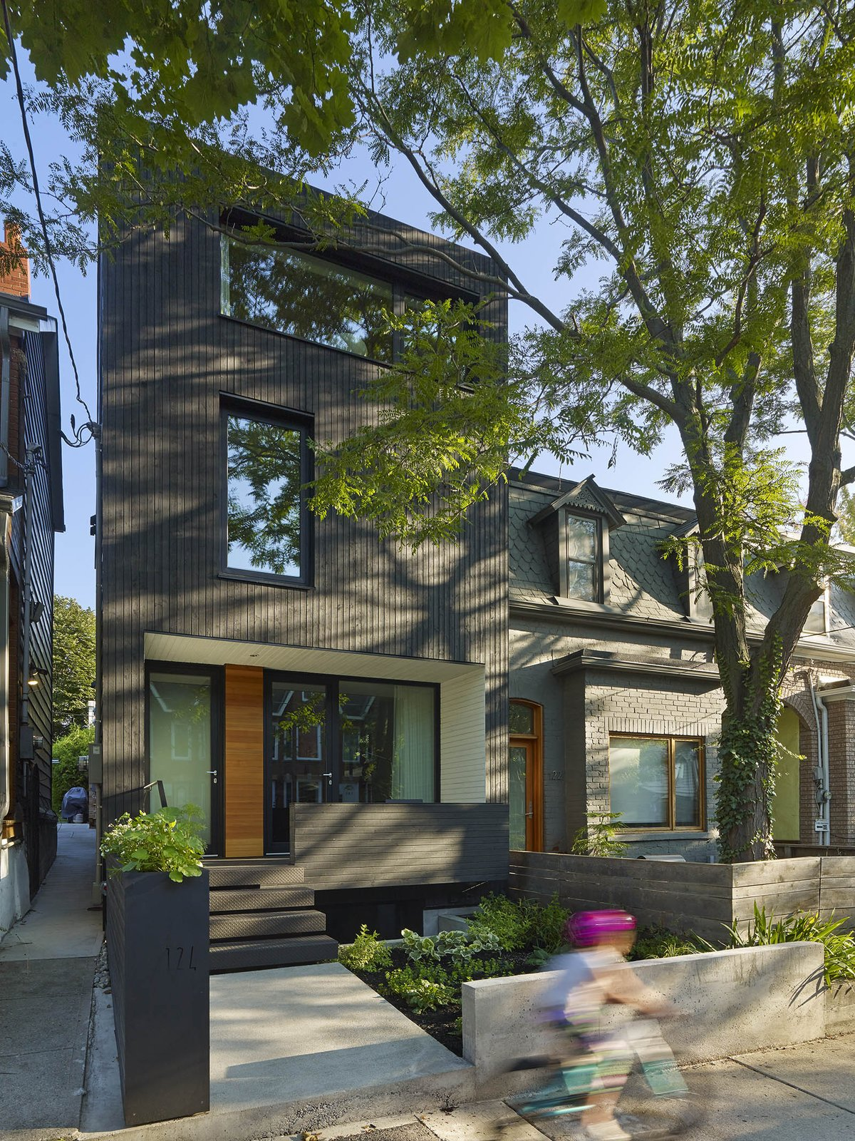 The all-black exterior cladding creates a quiet pause in the streetscape. By day, it acts as an abstract canvas for shadow play from the boulevard trees. By night, it has the quality of an austere lantern.