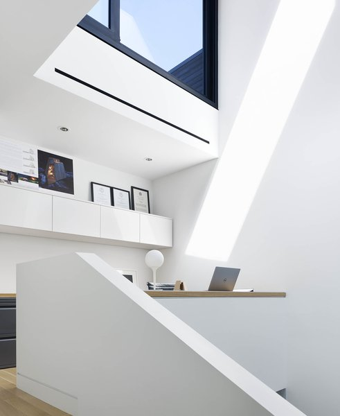 A home office occupies the light well, with views to the living room above, and a library space below. What would typically be the dark middle of the house is bathed in sunlight and enjoys a feeling of expansive vertical space.