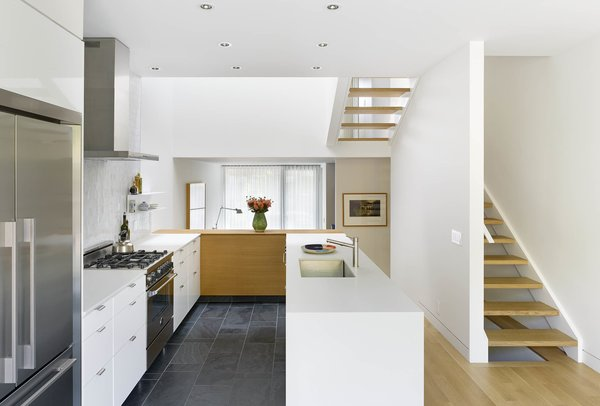 The split level ground floor results in a raised kitchen/ dining area with 9' high ceilings, and an intimate sunken library connected to the front terrace. Both areas receive plenty of sunlight from the light well above.