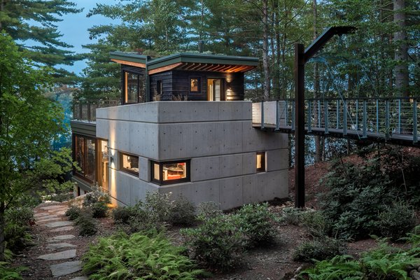 """A southern view shows the exposed concrete foundation and entrance bridge. """"As you approach and enter, the front door is at the top,"""" explains Sokol. """"It's a three-story house with the entrance on the third story, and the master bedroom in the basement—it's sort of upside down."""""""