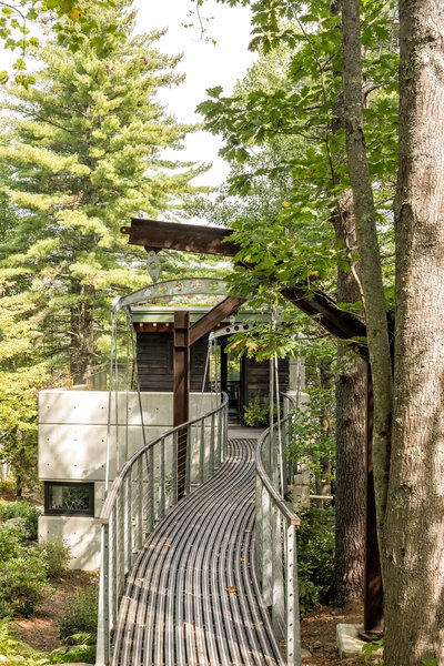 """The suspension bridge entrance. """"You're sort of suspended over the landscape, walking over all these rhododendrons and stones and shrubs and trees that are below you,"""" says Sokol. """"You're kind of up in the treetops, and that's how you arrive at the house."""""""