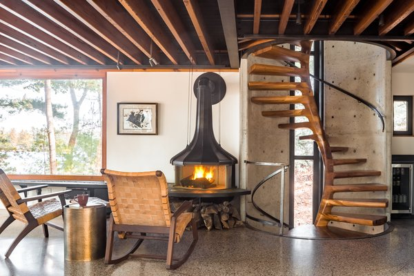 The staircase intersects the living room next to a wood-burning hearth by Andrew White.