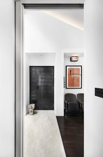 A lit Exit sign and salvaged cinema seats decorate the foyer, giving the home a playful feel.