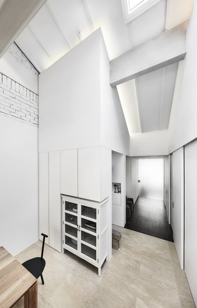 The use of white unifies the plan and enhances the feeling of spaciousness. Existing travertine and stained timber mark the apartment's former layout as a nod to its heritage.