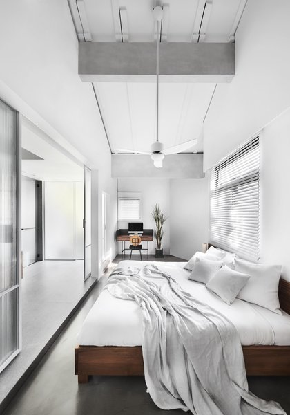 The white palette brings tranquility into the master bedroom. The loftiness of the ceiling continues here, with highlighted beams to continue the industrial aesthetic.