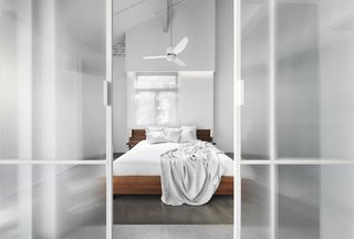 Opposite the bed is the generous bathroom, accessed through fluted glass sliding doors.