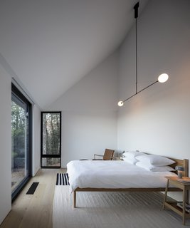 Aside from the natural light, the master bedroom is illuminated simply with a graphic Mobile Chandelier No.2 from Michael Anastassiades and a Bellhop table lamp from Flos. These accompany a Cove bed from Design Within Reach, a  Harlosh bedside table from Pinch Design, a Colonial armchair from Carl Hansen & Søn, and a rug from Calvin Klein Home.