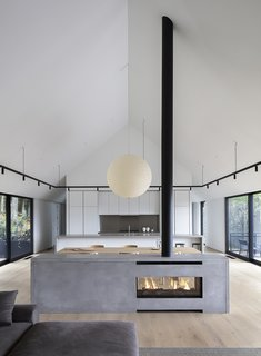 A central fireplace, designed as a minimal, gray block and visible from both sides, subtly separates the living and dining zones.