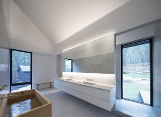 Timber accents in the lofty master bathroom comprise a simple Muji bench and a Hinoki wood soaking tub.