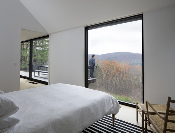 The master bedroom is tucked at one end of the house's long plan, and it shares valley views with the living room.