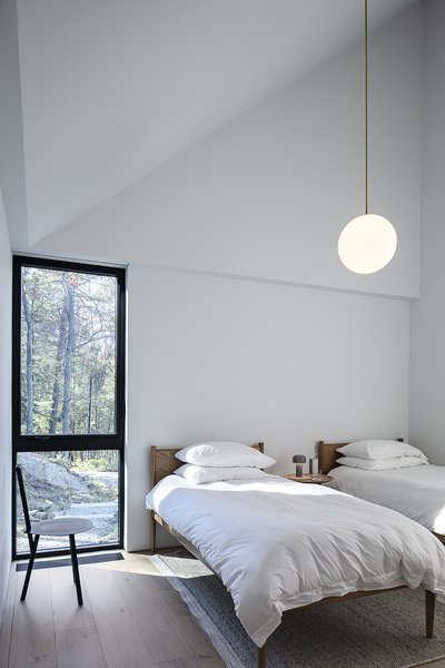The guest bedroom features a Cove bed from Design Within Reach, a Spade chair by Faye Toogood, a Dune rug from Hem, and a Michael Anastassiades pendant lamp.