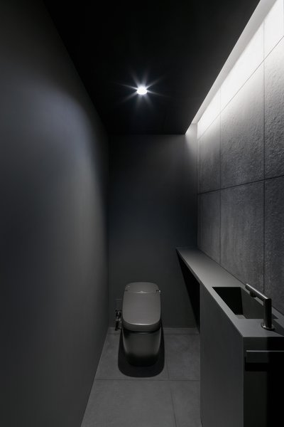 A bathroom tucked beneath the stairway has a cavernous quality. Everything—down to the toilet and Hansgrohe AXOR faucets—has the same charcoal shade.
