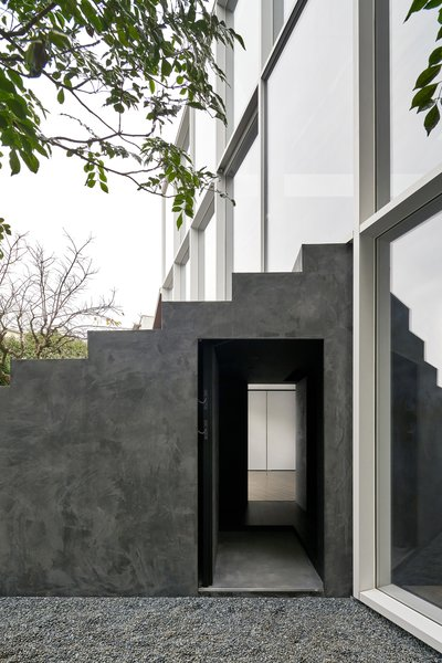 The subtle front door blends seamlessly into the staircase. It leads to the first story, where the client's elderly parents stay so that they don't have to walk up many flights of steps.