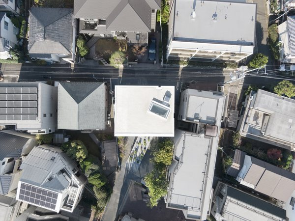 An aerial view shows the neighborhood's density and the relationship of the house with the lane in front of it.