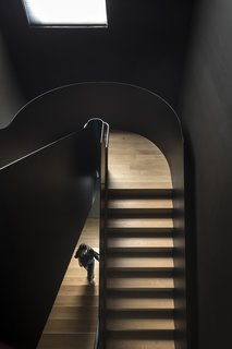 The staircase is offset from the straight walls to emphasize its curvaceous lines.
