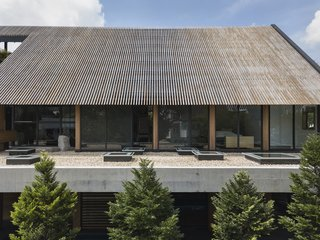 The mono-pitch roof extends past the glazing to shelter the interiors from extreme sunlight and rain.