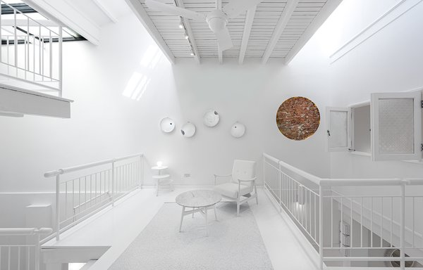 Midcentury furniture and the vintage ceramic plates mounted on the wall are also painted white, again flattening the distinction between old and new.