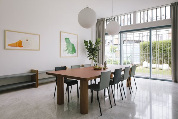 In Still House, simple forms and jovial colors create a warm, friendly space. Here, a custom-designed dining table with exaggerated legs is matched with Vitra .03 dining chairs designed by Maarten Van Severen.