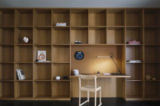 Made of oak, a wall of shelves accommodates an office nook accented with a slim Superlight table lamp from Pablo.