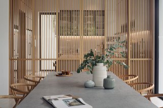 An elegant timber screen at the kitchen maintains a sense of porosity, as well as lets in light and breeze while filtering kitchen mess or activity. The tactility of the Carl Hansen Wishbone dining chairs matches the kitchen screen panels.