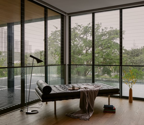 The window and handrail details are minimal to enhance the indoor-outdoor relationship. The furniture are equally streamlined; in the lounge is a Louis Poulsen AJ floor-standing lamp and Knoll Barcelona day bed.
