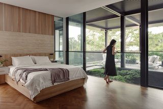 The master bedroom on the second storey has privacy buffer with the placement of the generous patio and tree void upfront. The custom bed frame designed by Stacey Leong Interiors continues the architecture's linear language.