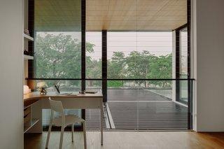 悬垂的网格详细减轻眩光,同时让过滤视图和光线通过。干净的设计吸引眼球着对面的房子的树木。