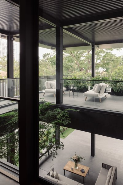 The tree void allows a strong visual connection between the first and second storeys. It enhances the house's sense of spaciousness as well as green features. The outdoor furniture is from Danish Design Co.