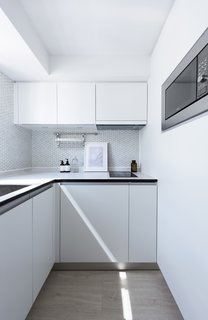 Each apartment's kitchen is modest in size. The all-white palette reflects light around the space.