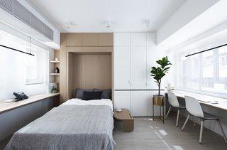 灯具和细木工的黑色口音创造了整个白色和木材空间中有趣的焦点。整洁的设计使空间宁静,有利于工作和放松。