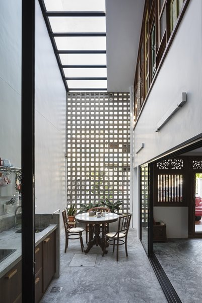A new semi-outdoor space is created by enclosing the former house's foyer with a skylight and concrete breeze-block screen. It functions excellently as a wet kitchen, with cooking smells filtering through the screen.