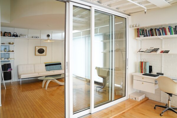Before: A sliding glass door with a white aluminum frame separated the guest room from the kitchen.