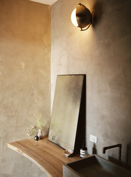 In the guest bathroom, a light scone from West Elm hangs on lime-washed walls.