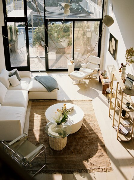 Architect Amanda Gunawan's 1,620-square-foot Biscuit Loft in Downtown L.A. is awash in gentle light. Designed by French-born, Missouri-based architect E.J. Eckel in 1925, the building had been converted by Aleks Istanbullu Architect in 2006 into a live/work complex. Amanda introduced Japanese-inspired touches to soften the industrial language. The harmonious living room features a CB2 sofa, white Eames Lounge Chair and Ottoman, Knoll Wassily Chair, and a rug and timber bench from Zara Home.