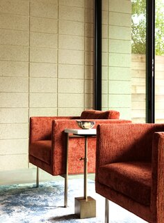 A set of rust-colored chairs contrast with the neutral-toned concrete wall in the living room.