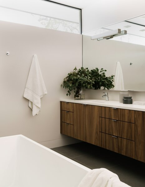 Walnut cabinets and quartz counters in the primary bathroom incorporate non-toxic, water-based finishes.