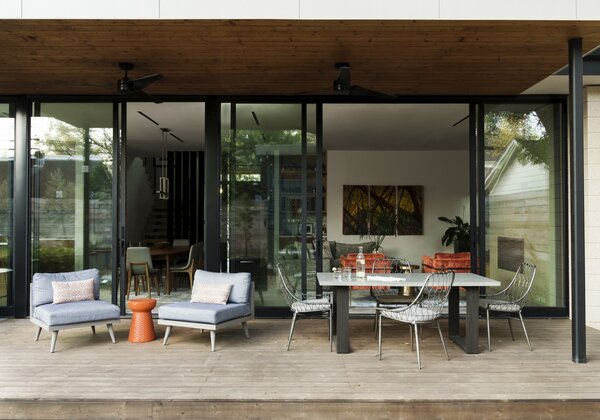 """""""The seamless connection between the interior living spaces and the covered patio blurs the divide between indoors and outdoors,"""" says Britt. The pine deck includes an area for al fresco dining around a concrete table by West Elm with metal chairs by Four Hands."""