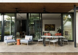 """The seamless connection between the interior living spaces and the covered patio blurs the divide between indoors and outdoors,"" says Britt. The pine deck includes an area for al fresco dining around a concrete table by West Elm with metal chairs by Four Hands."