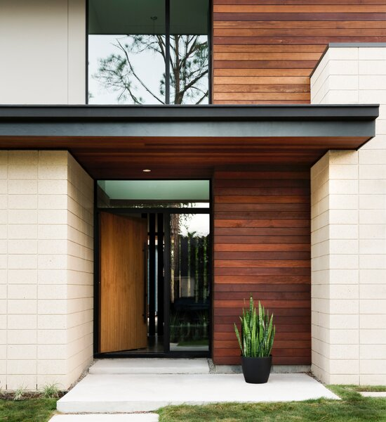 """At the McClendon Residence's entrance, ipe wood siding and soffits contrast with light concrete-block walls. """"We used natural materials and colors for a modern aesthetic that would fit in with the neighborhood,"""" explains Andrews. """"As you approach, the house is subtle and quiet rather than being ostentatious and loud."""""""