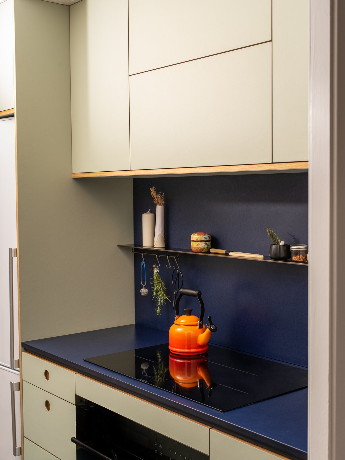 Raising the cabinet height and installing new color-blocked Richlite counters and full-height backsplash help the kitchen feel larger.