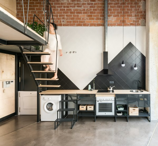 The public area of the apartment, which includes the kitchen, has an open floor plan. The floor is a simple concrete solution used in garages which, combined with brass profiles to prevent cracks, unifies the whole floor of the apartment.