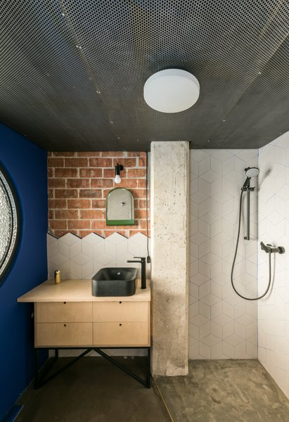 The bathroom is the only fully enclosed room in the apartment, and it sits below the new mezzanine level. Geometric tiles have been used to create a playful backsplash against the raw brick wall behind the sink.