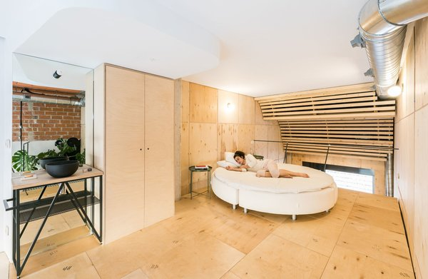 The most intimate and restricted area of the apartment is the bedroom on the new mezzanine floor. Over 100 recycled plywood lids were used as cladding in the downstairs studio—the wall of which continues into the bedroom—and for the bedroom floor.